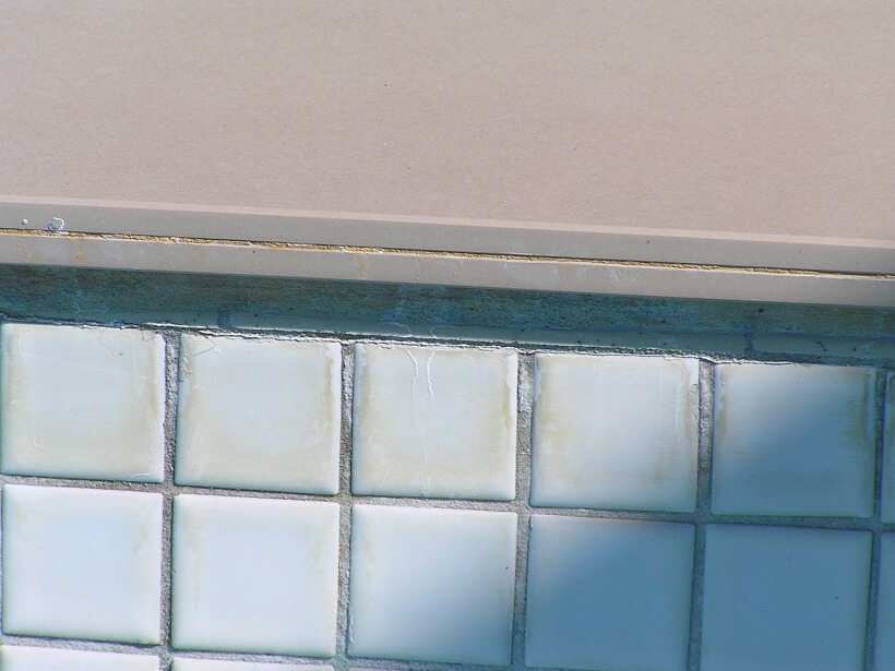 Showing telltale efflorescence on tile grout indicating water passing out from pool shell.